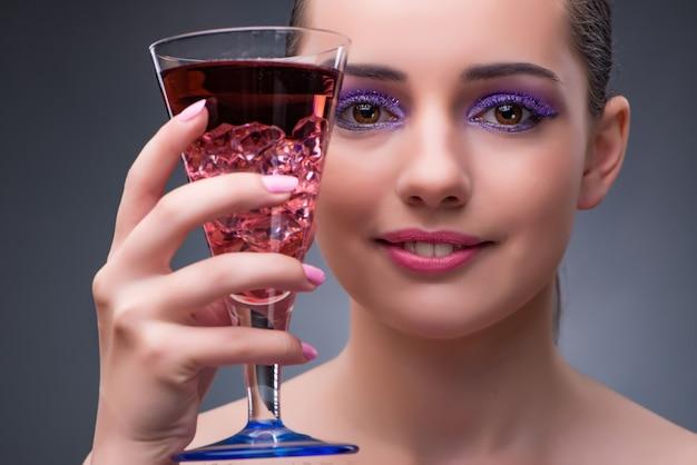 Bela mulher bebendo coquetel vermelho Foto Premium