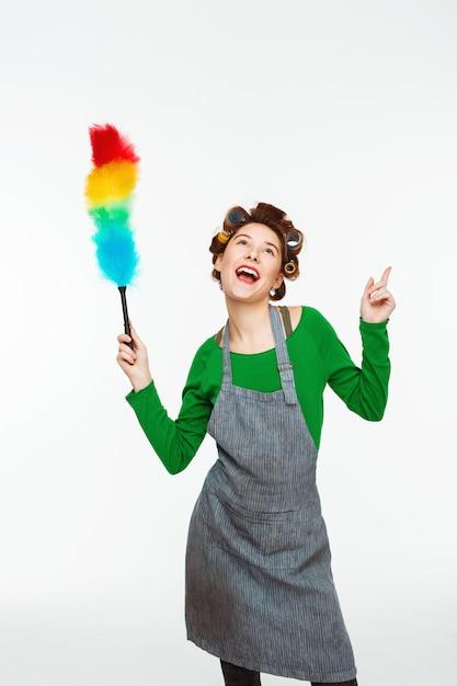 Bela mulher branca canta músicas e dança durante a limpeza Foto gratuita