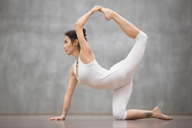 Bela mulher de iogue fazendo pose de chakravakasana Foto gratuita