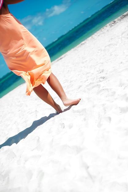 Bela mulher de vestido andando perto do oceano da praia em dia de verão na areia branca Foto gratuita