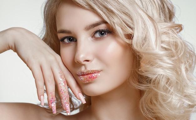Bela mulher loira encaracolada com maquiagem de arte perfeita, design de unha fosco na moda com glitter. Foto Premium