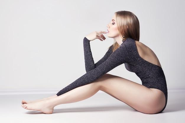 Bela mulher loira sexy. menina sentada no chão Foto Premium