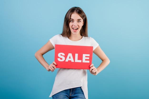 Bela mulher morena com banner de sinal de venda copyspace isolada sobre azul Foto Premium