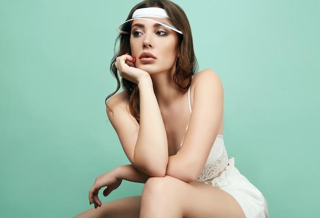 Bela mulher morena sexy com lábios suculentos em forma de esporte branco Foto Premium