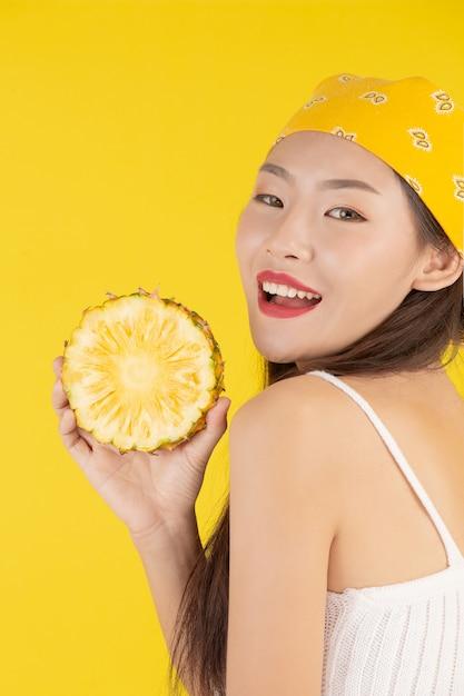 Bela mulher segurando um abacaxi Foto gratuita