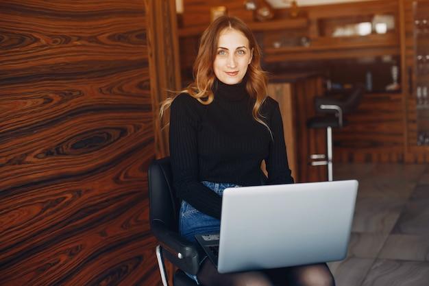 Bela mulher sentada em casa com laptop Foto gratuita