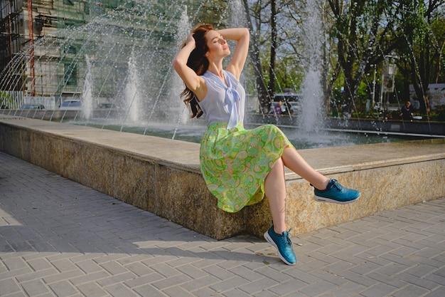 Bela mulher sentada perto da fonte Foto gratuita