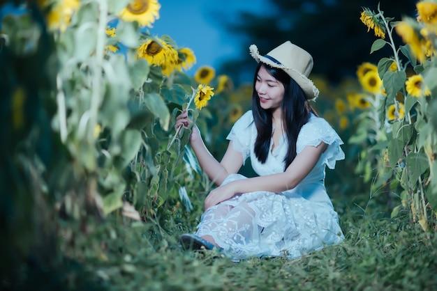 Bela mulher sexy em um vestido branco, andando em um campo de girassóis Foto gratuita
