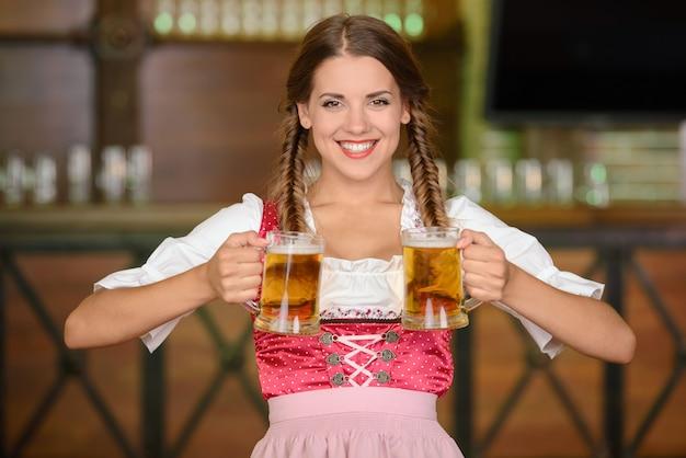 Bela mulher sexy garçom segurando copos de cerveja. Foto Premium