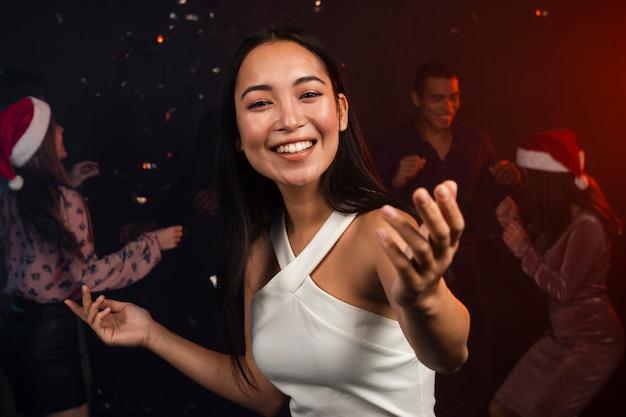 Bela mulher sorridente dançando na festa de ano novo Foto gratuita