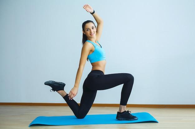 Bela mulher sorridente fazendo yoga dentro de casa no ginásio Foto Premium