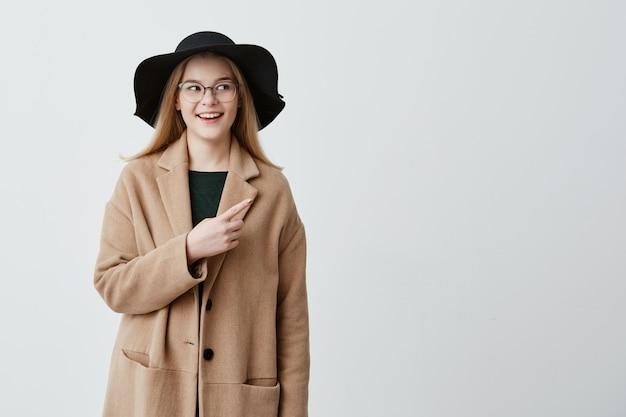 Bela mulher sorridente no casaco verde camisola e óculos, apontando para a parede branca em branco enquanto demonstra algo. fêmea nova alegre que indica com o dedo dianteiro no fundo cinzento. Foto gratuita