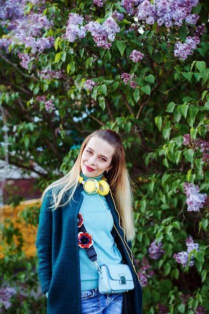 Bela mulher sorridente usando fones de ouvido amarelos sob o arbusto lilás Foto Premium
