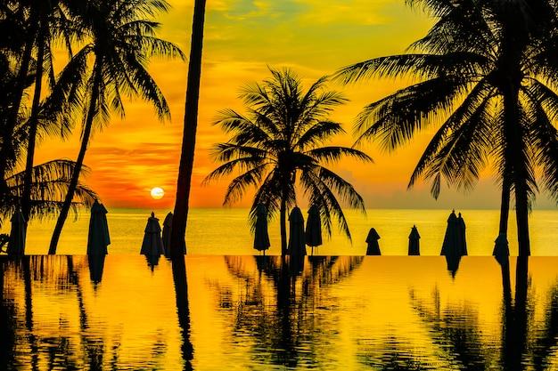 Bela natureza ao ar livre paisagem com mar oceano e coqueiro ao redor da piscina no sunrsie ou pôr do sol Foto gratuita