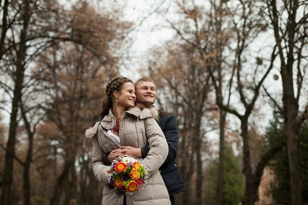 Bela noiva e noivo ucraniano em trajes de bordados nativos no fundo de árvores em um parque, cerimônia de casamento tradicional Foto gratuita