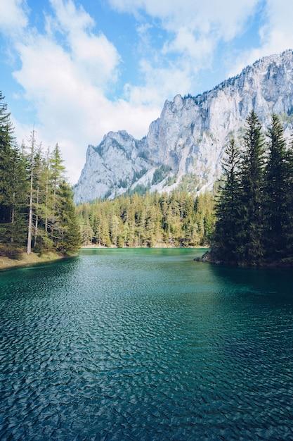 Bela paisagem com um lago em uma floresta e incríveis montanhas rochosas Foto gratuita