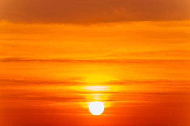 Bela paisagem do sol ardente e céu laranja acima dele Foto Premium