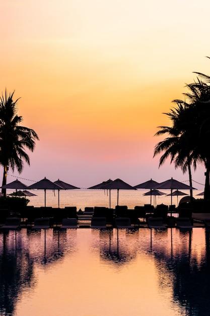 Bela piscina ao ar livre com cadeira de guarda-chuva silhueta ao redor no resort no tempo do nascer do sol Foto gratuita