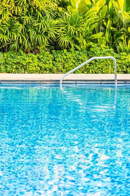 Bela piscina ao ar livre com cama espreguiçadeira e guarda-chuva no resort para viagens e férias Foto gratuita
