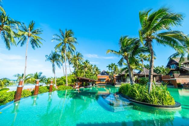 Bela piscina ao ar livre com palmeira de coco Foto gratuita
