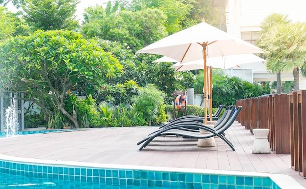 Bela piscina de hotel de luxo com guarda-chuva e cadeira Foto gratuita