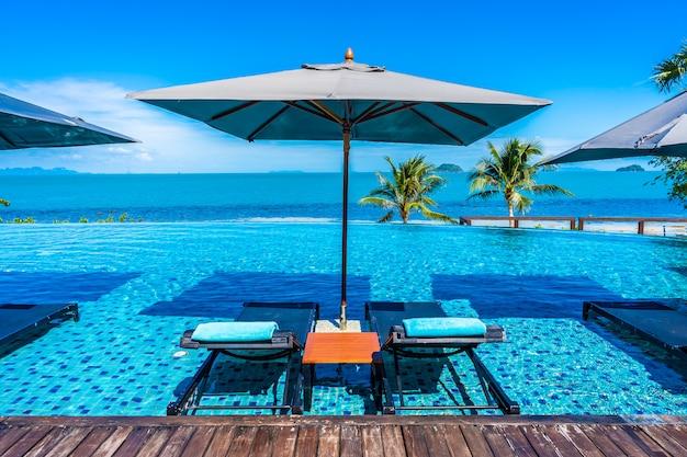 Bela piscina de luxo ao ar livre no resort hotel com oceano mar em torno de palmeira de coco e nuvem branca no céu azul Foto gratuita