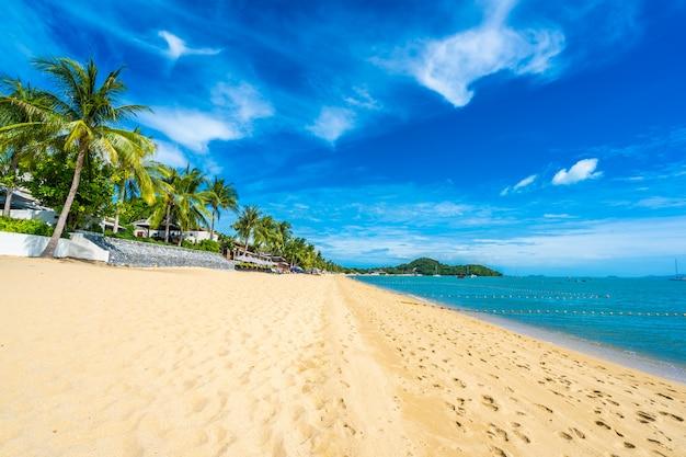 Bela praia tropical mar e oceano com coqueiro e guarda-chuva e cadeira no céu azul Foto gratuita