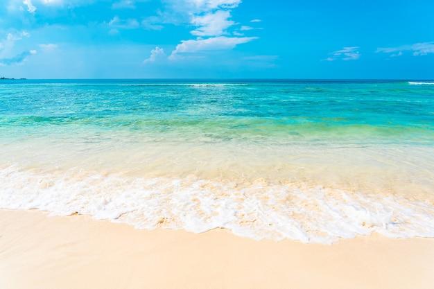 Bela praia tropical vazia, mar oceano com nuvem branca no fundo do céu azul Foto gratuita