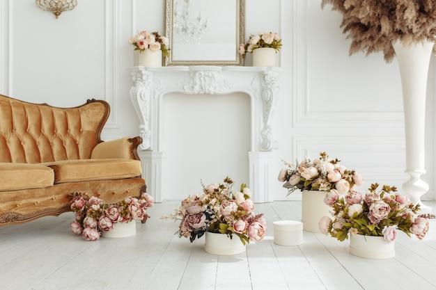 Bela provance sala de estar com sofá marrom perto da lareira com flores e velas Foto gratuita