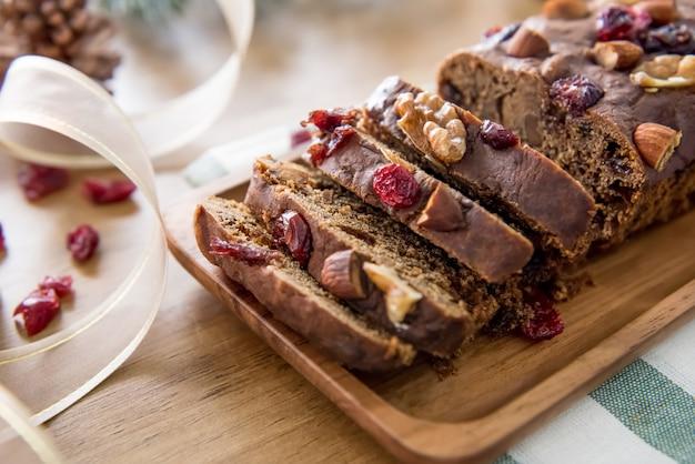 Bela saborosa caseira mista porca bolo de frutas secas na mesa de madeira Foto Premium