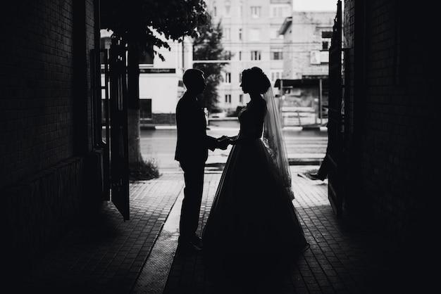 Bela silhueta de um casal apaixonado, noiva e noivo no dia do casamento Foto Premium