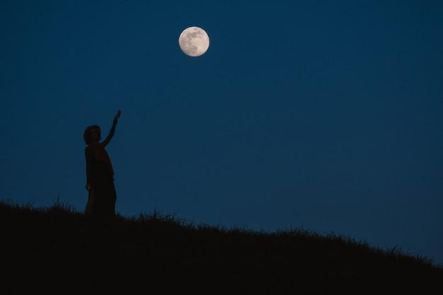 Bela silhueta de uma jovem contra um fundo de céu noturno com lua cheia Foto Premium