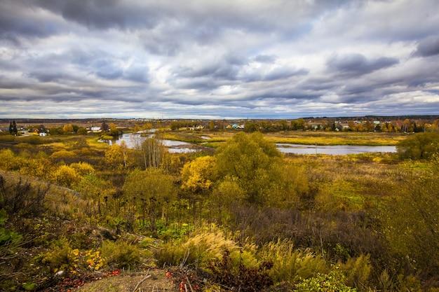 Bela vila na rússia no outono, com as belas árvores amarelas sob o céu nublado Foto gratuita