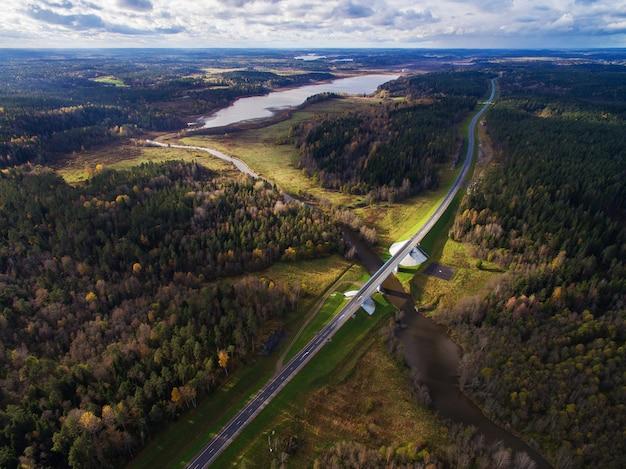 Bela vista aérea da ponte rodoviária sobre o rio rodeado por floresta Foto Premium