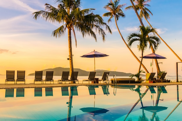 Bela vista ao ar livre com guarda-chuva e cadeira ao redor da piscina em hotel de luxo Foto gratuita