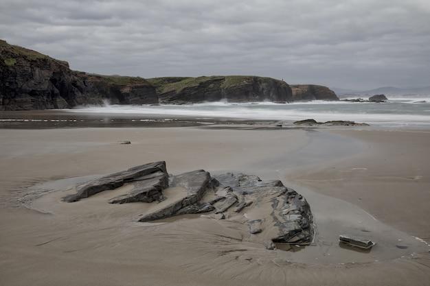 Bela vista da bela praia de os castros em um dia nublado em ribadeo, galiza, espanha Foto gratuita