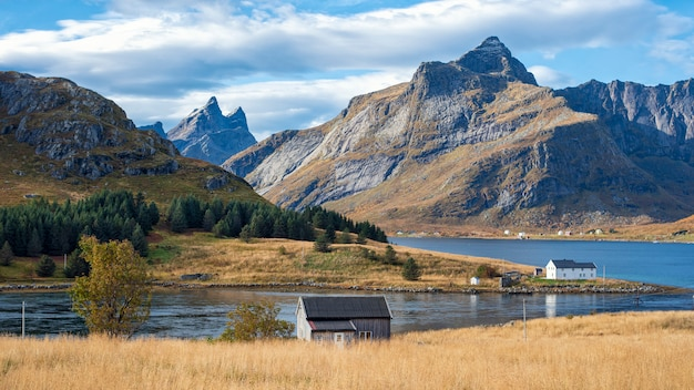 Bela vista da casa norueguesa e montanha nas ilhas lofoten, noruega Foto Premium