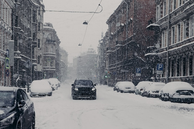 Bela vista da maravilhosa cidade nevada com automóveis cobertos de neve Foto Premium