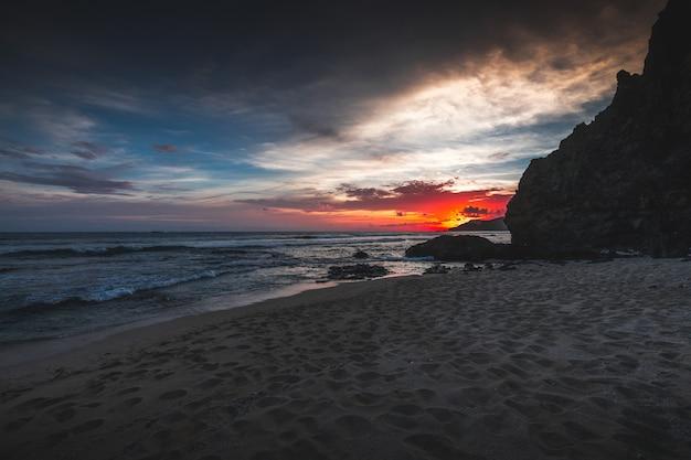 Bela vista da praia e do oceano ondulado ao pôr do sol capturado em lombok, indonésia Foto gratuita