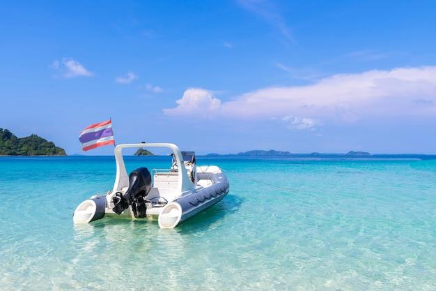 Bela vista da praia ilha de koh chang e barco para turistas seascape na província de trad oriental da tailândia sobre fundo de céu azul Foto gratuita