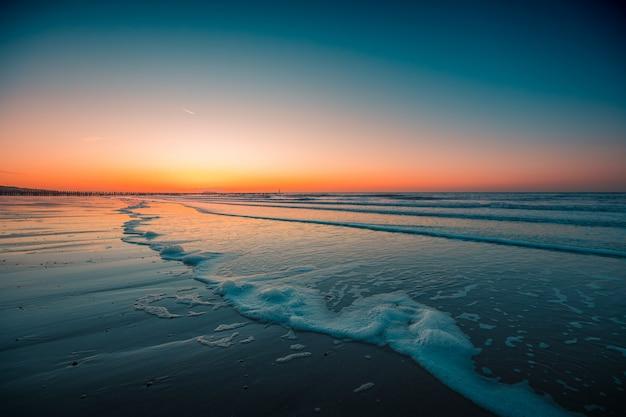 Bela vista das ondas espumosas na praia sob o pôr do sol capturado em domburg, holanda Foto gratuita