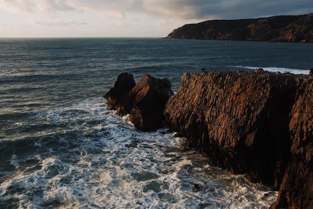 Bela vista das rochas ao pôr do sol com o mar ao fundo Foto gratuita