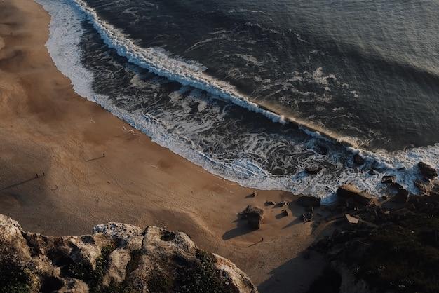 Bela vista de grandes ondas quebrando em uma praia ao pôr do sol Foto gratuita