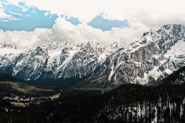 Bela vista de montanhas cobertas de neve com incrível céu nublado Foto gratuita