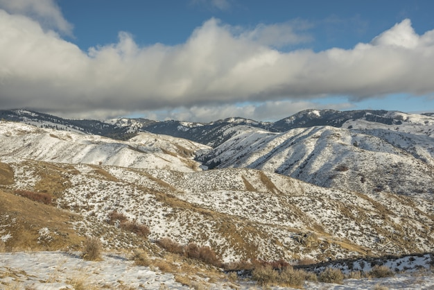 Bela vista de montanhas nevadas com um céu nublado azul durante o dia Foto gratuita