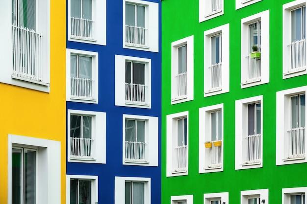 Bela vista de prédios de apartamentos em cores vivas com janelas com moldura branca em um dia frio Foto gratuita