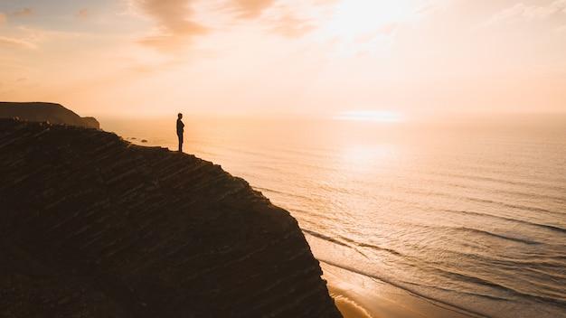 Bela vista de uma pessoa em pé em um penhasco sobre o oceano ao pôr do sol no algarve, portugal Foto gratuita