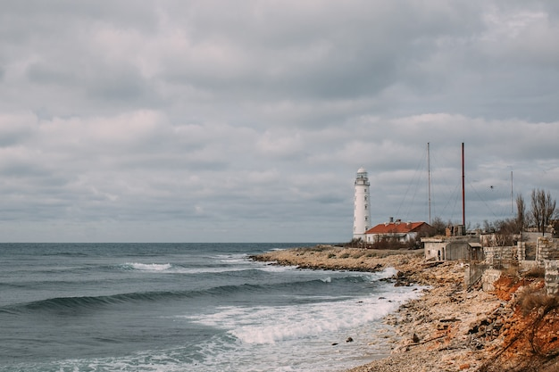 Bela vista do mar com um farol branco e edifícios antigos na costa. há um mar ondulado abaixo e um céu nublado acima Foto Premium