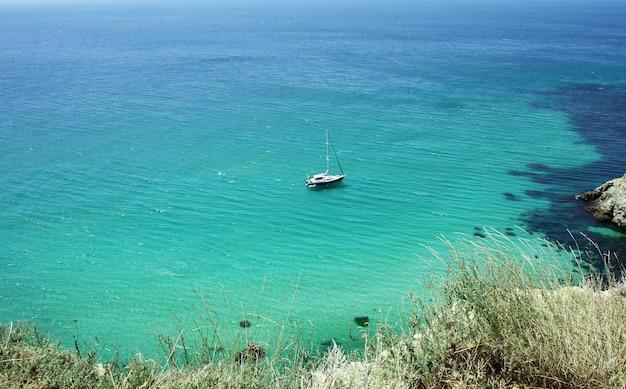 Bela vista do mar com um iate, água azul transparente e areia branca Foto Premium