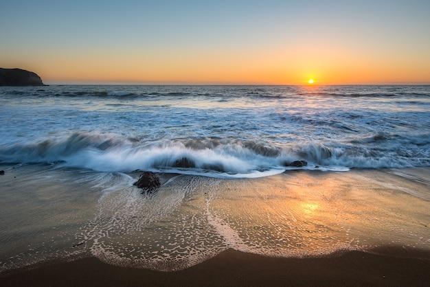 Bela vista do mar da costa oeste no oceano pacífico durante o pôr do sol Foto Premium